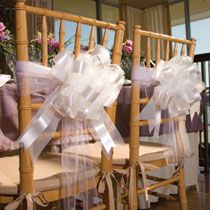 we simply wrapped some tulle ribbon around the chair several times and tied it into a knot, then attached the pull bow to the tulle.