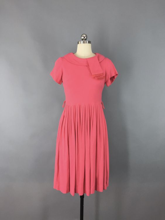 Vintage 1950s day dress in a coral pink wool knit, it's possibly a wool blend. Short sleeve, turned collar with fringed detail, pleated skirt, side belt loops but no original belt and back metal zippe