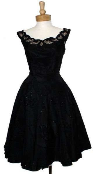 ~An elegant and magnificent 1950's cocktail dress in black taffeta and lace~ Fitted bodice with positively exquisite detail at the neckline, illusion lace covered with quilted taffeta appliques edged in shimmering black beads, full skirt with beaded lace appliques on the front, boned bodice. No maker label.
