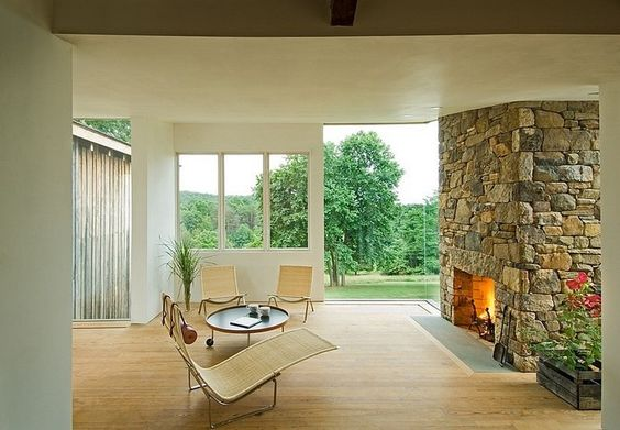 An Inspiring Exposed Stone Firepit Design For Living Room With Wooden Flooring And Exciting Easychair With Unique Round Wooden Table Also Glass Windows Beautiful Village House with an Eclectic Sense Home design http://seekayem.com