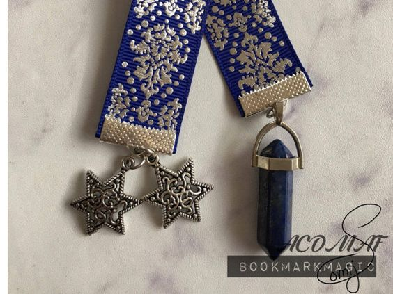 A Court of Mist and Fury Ribbon bookmark with matching charms. Each bookmark is made personally by me and with a bright Blue ribbon with silver details. And with silver charms to give a nice match to the silver detailing on the ribbon. Each one has a two silver stars on one side and a pointed Lapis Lazuli crystal on the other side. Ribbon: Grosgrain Ribbon, Blue with elegant silver details on one side. Size: The bookmark comes in to sizes one in 25 cm and one in 28 cm for those book that are ...:
