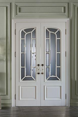 белая дверь из массива со стеклом со сложным обкладным