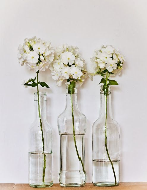 Save money on flowers by have bottle-neck vases and just one flower in the bottle. Elegant, simple.