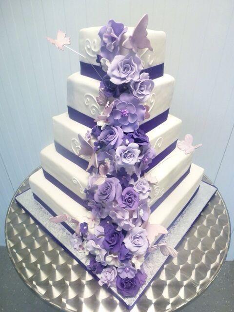 Vierkante bruidstaart met paarse bloemenwaterval