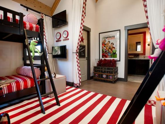 This kids bedroom from HGTV Dream Home 2014 is inspired by the Muppets. While sticking to a sophisticated color palette of red, white and black, this room bursts with kid-approved details like Muppets accessories, a curtained-off play area and a TV for each bunk!