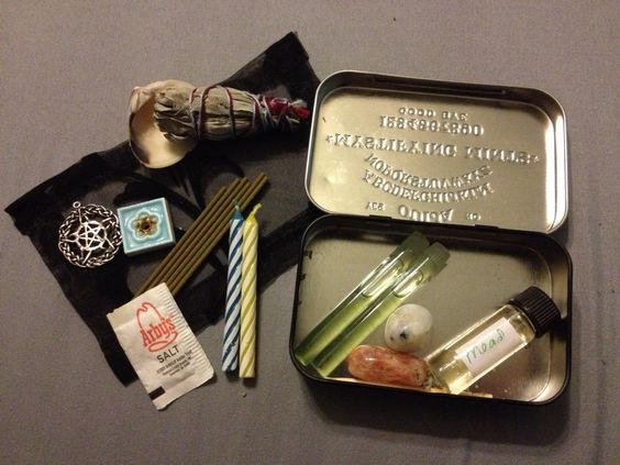 """My homemade """"Altoid"""" traveling altar. The mint case actually has the classic Ouija board on the lid with """"Mystifying Mints"""" printed on the middle. Items inside include: Mini sage bundle, sea shell for ashes or offerings, incense holder and sandalwood incense, pentacle, salt, altar cloth, mead, altar oil (in small vials), sun- and moonstones, and God & Goddess (birthday) candles. Karen made little star-shaped holders for the candles that aren't in the picture."""