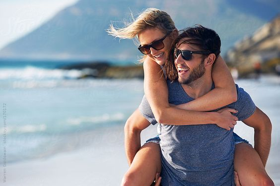 beach laughing couple by Warren Goldswain