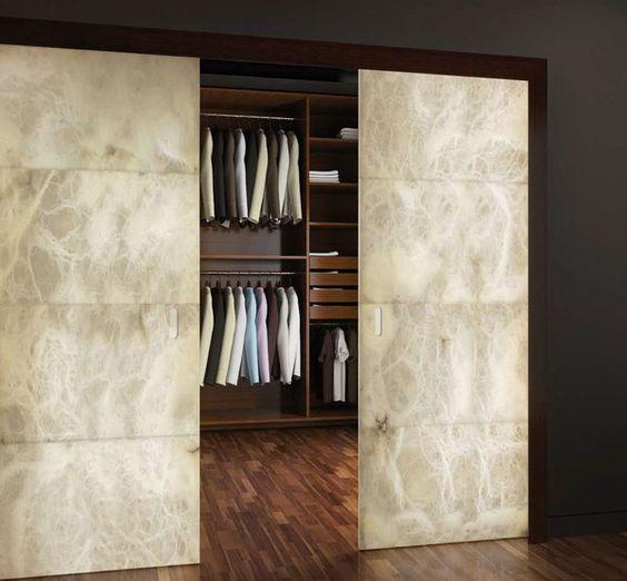 Version dressing, les panneaux d'albâtre coulissent avec élégance pour venir masquer les étagères