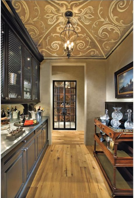 This narrow butler's pantry is adorned with an intricately painted ceiling.: