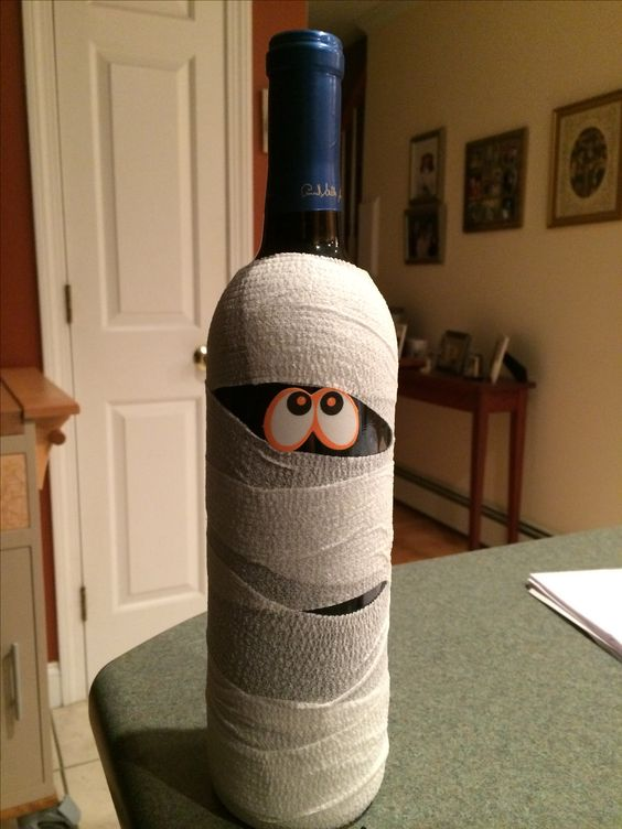 Halloween mummy wine bottle  Bottle of wine, self-adhering tape and googley eyes. Glue eyes on, wrap bottle with tape...Have fun!  Super easy! Great gift idea for Halloween party!