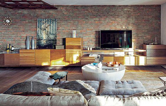 Um aparador alongado apresenta diferentes madeiras e volumes. O móvel ocupa toda a extensão da sala e serve como apoio para a TV, quadros e bar. Desenho da arquiteta Fabiana Avanzi