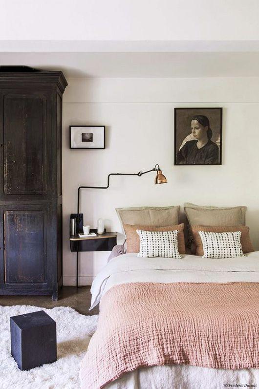 Black armoire, blush pink bedding, white room