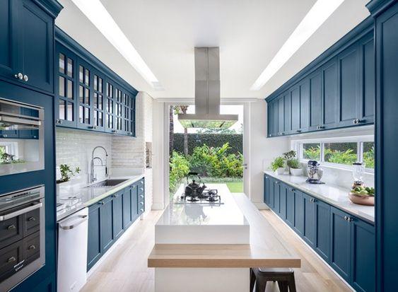 Cozinha gourmet tem armários em laca azul marinho da Digiovanni Móveis e Marcenaria. Piso de madeira e bancada claros equilibram a cor. (Foto: Divulgação)