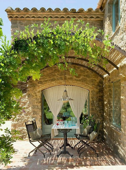 Arched pergola over stone farmhouse patio dining area. Romantic French Country Garden Courtyard Ideas. #frenchcountry #courtyard #dining #vines
