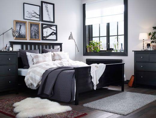 Lit brun-noir habillé d'une couette houssée beige et blanc et d'un couvre-lit gris foncé, commodes brun-noir et lampes en acier nickelé dans une chambre à coucher spacieuse