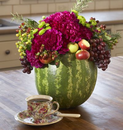 A Fruity Flavor    Materials  •Medium-size watermelon  •Florist foam  •Chicken wire  •Florist picks  •Magenta carnations  •Assorted fruit (such as lady apples and grapes), small flowers, and berries