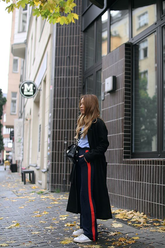 Outfit: The Sport-Luxe Trousers. Desi is wearing side stripe pants, button down shirt, oversized coat and stan smith sneakers