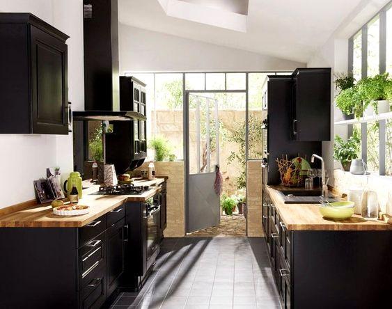 Une cuisine noire et bois ouverte sur l'extérieure, très lumineuse, qui rappelle une serre.