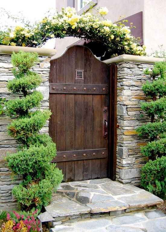 Garden gate inspiration: a French Country style garden gate is rustic with straps and clavos and flanked by topiaries. #gardengate #frenchcountry #rustic #secretgarden