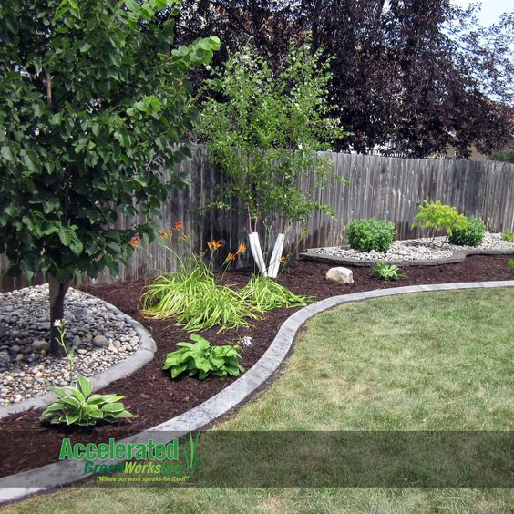 Use extra edging (in this case gray concrete curb with a slant) and alternate between rock and mulch to add definition and create a fun, artistic design along your backyard fence.