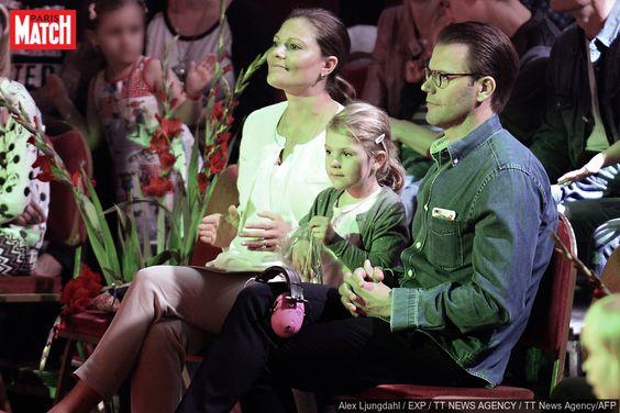 Assise entre sa maman la princesse Victoria de Suède et son papa le prince…
