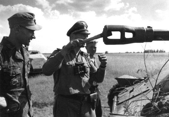 """Union Soviétique, Un """"SS-Hauptsturmführer"""" glisse une grenade (Stielhandgranate M24) dans un affut de canon russe de prise pour le rendre hors combat"""