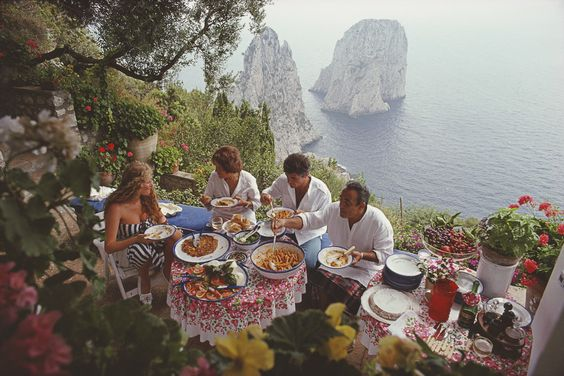 Italian artist and actress Domiziana Giordano, Francesca Sanvitale, Dino Trappetti and Umberto Terrelli dining al fresco on a terrace overlooking the waters off the coast of the island of Capri, Italy:
