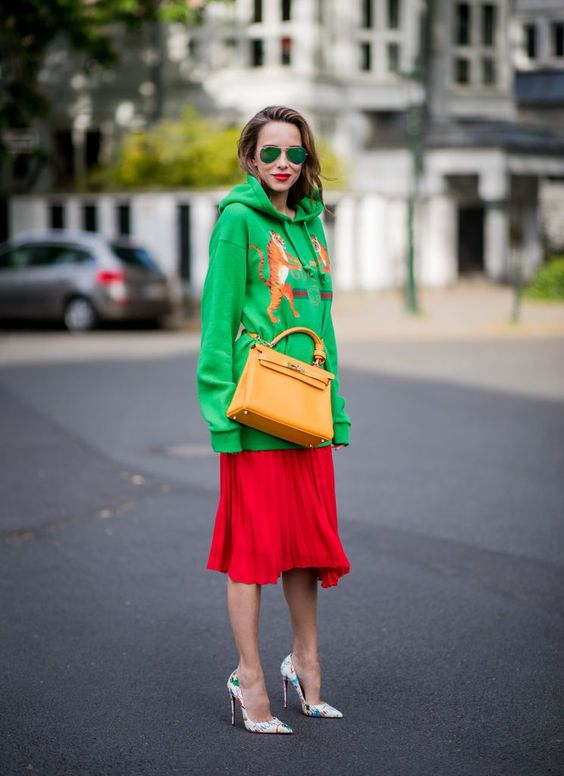 Street style fashion woman wearing a Gucci sweatshirt and pleated skirt