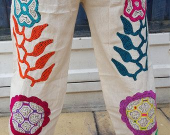 Shipibo ceremony trousers, featuring Ayahuasca, Chacruna and the anaconda in colourful embroidery in a range of colours. There are also sacred Icaros on various parts of the outfit.   https://www.etsy.com/uk/listing/456881568/ayahuasca-white-ceremony-unisex-trousers?