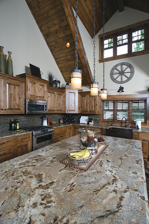 Kitchen from the Whitefish Chain of Lakes Home Featured in the August/September issue of Lake and Home Magazine: knotty alder distressed cabinets, granite countertop, slate backsplash and 24 foot peaked ceilings with knotty pine beams