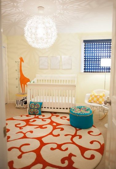 A contemporary gender neutral nursery. The beige wall creates an air of calmness and enhances the visual flow of space in the room. The stunning, vibrant giraffe height chart wall sticker, serves as a unique focal point in the nursery, which will provide mental and visual stimulation for the baby. The ultra chic rocking chair and white nursery suite reinforce the style and completes the look.
