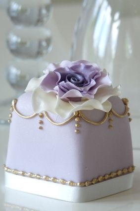 """Purple Dream"" - lilac cake with hand painted gold detail. Rachelle's Beautiful Bespoke Cakes will ""mix and match with a co-ordinating cupcake design or fresh flowers to create a stunning centrepiece. Mini cakes are available in fruit, lemon, vanilla or chocolate.""  £ 9.50"
