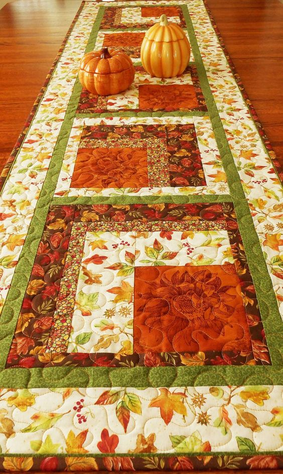 This quilted autumn table runner is extra wide and long - perfect for your fall or Thanksgiving table. Beautiful russet sunflowers are featured in each block and surrounded by fall leaves, berries, and acorns, along with a multi-colored cobblestone print and a green tiny scroll print. The size is approximately 20 X 70 (51 X 178 cm). It can span your dining room table or drape off the ends of a shorter table, or it can be used as a bed runner. I machine-quilted an all-over meander in gold thr...