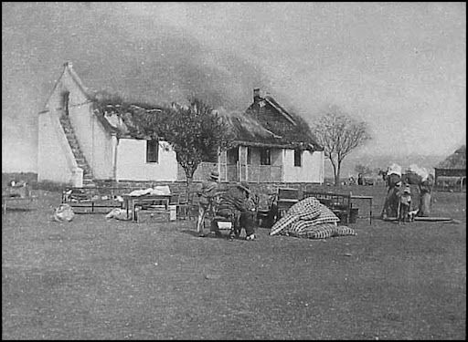 Anglo Boer War - Scorched earth campaign by the British against Boer women and children. a Boer family with a few belongings they were allowed to keep, watch as their home is torched by the British.: