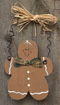 Painted wood in a gingerbread man shape with fabric bow accent. Ornament has curly metal hanger and a raffia bow attached to the hanger. Gingerbread Man ornament measures 4inches high.