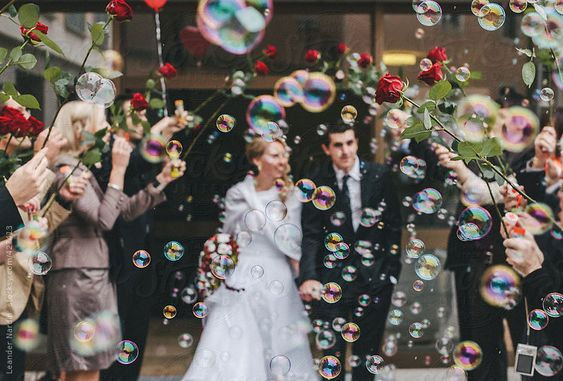 friends celebrating just married couple with soap bubbles and red roses by Nox | Stocksy United