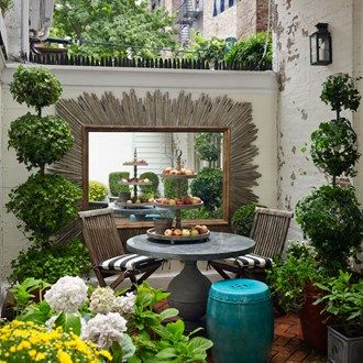 The second smallest house in Manhattan featuring a small enclosed garden with ivy topiary