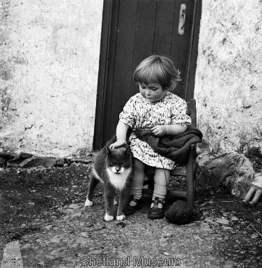 Knitting a DIFFERENT piece, in a different dress, different day, same doorway -- three year old Chrissie Cheyne, in the Shetland Islands during WWII, pauses to pet the same cat. Shot by photographer J. Peterson in Walls Parish, mate is at https://www.pinterest.com/pin/38702878017876316/