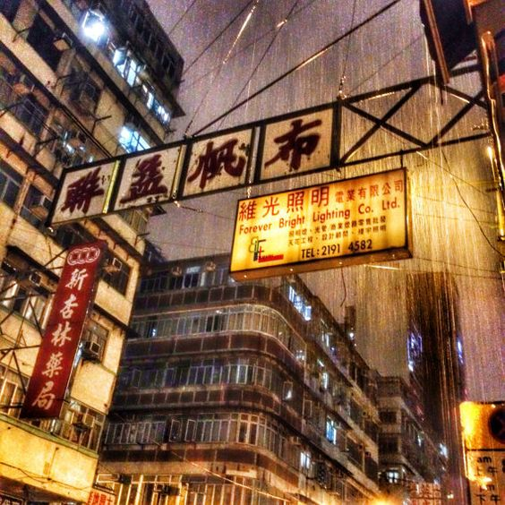 Forever Bright: A Vintage Sign in Hong Kong Blazes Through a Downpour