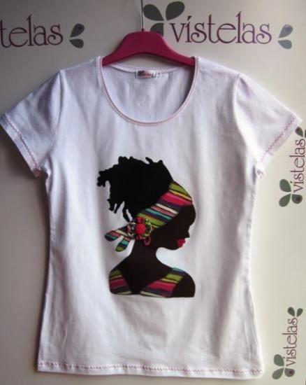 Camiseta blanca, de manga corta, talla L, con aplicación en patchwork de una silueta de mujer africana. Las telas, especiales para patchwork, combinan diferentes tonalidades de rosas lilas y turquesas, ideales para combinar este verano 2013. Se hacen todas las tallas, desde la S hasta la 3XL.