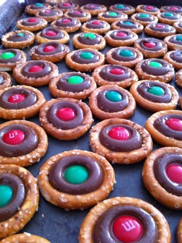 Round pretzels, Hershey kiss, and m&m.;  Super easy and cute with any color combo for any event.