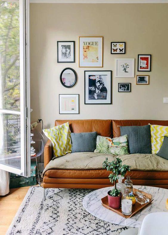 petit salon aménagé avec un canapé en cuir marron, coussins en gris et jaune, table basse en marbre blanc