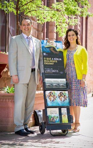 Dos testigos de Jehová predicando en la calle junto a un exhibidor de publicaciones