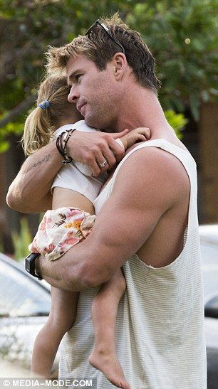 Cuddles with daddy: The brother of actors Liam and Luke enjoyed a hug from his eldest chil...