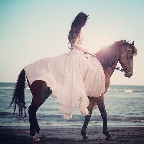 Fairytale portrait of a woman riding horse on the beach. Beautiful pink dress.: