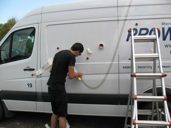 Applying vinyl decals to a van for Prowire.