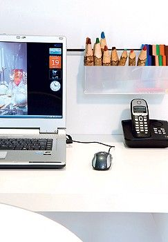 Painel multiuso - A mesa de trabalho está apoiada em uma prancha com perfis metálicos que servem para encaixar objetos e esconder os fios (Foto: Casa e Jardim)