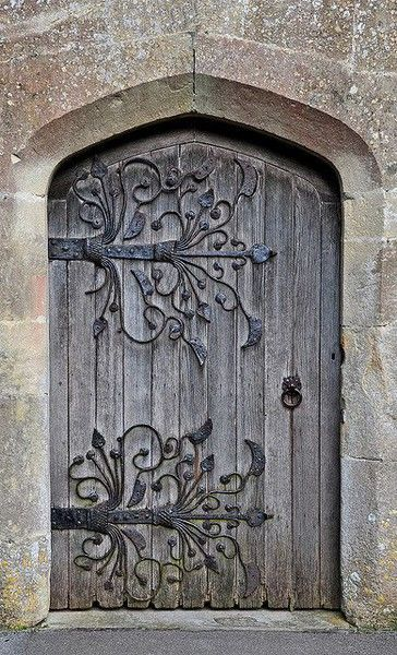 French Romanesque Door- Wonderful contrast of man cut stone, wood and organic metal as if the hinges were ivy covering the door.