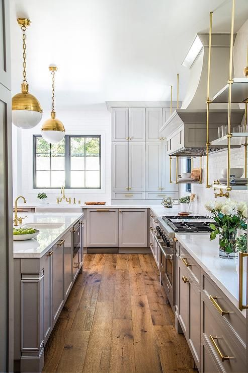 White and gray kitchen features two brass Hicks Pendants illuminating a gray center island topped with white quartz fitted with a farmhouse sink and brass gooseneck faucet.