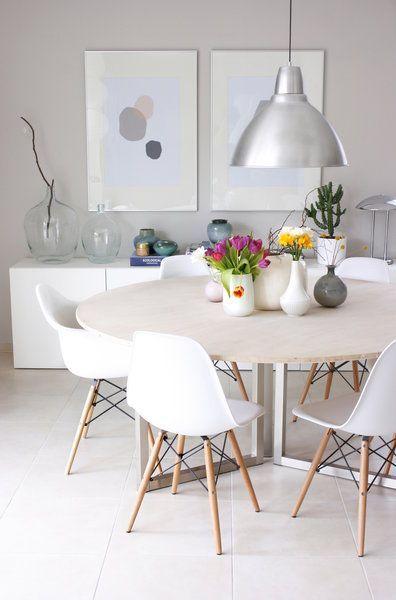 Wohn- Esszimmer Kombination in weiß. Gemütliche Essecke mit rundem Esstisch und Stühlen in skandinavischem Design. Aufgelockert durch die bunte Blumen in verschiedenen Vasen.